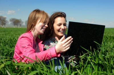 Two people smiling in a field with a laptop.